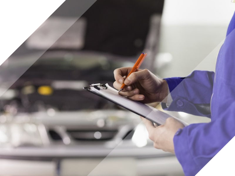 Technician writing notes about vehicle check